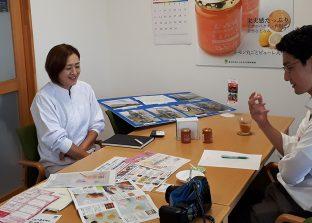 福島民友新聞の記者さんから取材をうける「ももれーど」開発者 芳賀(左)